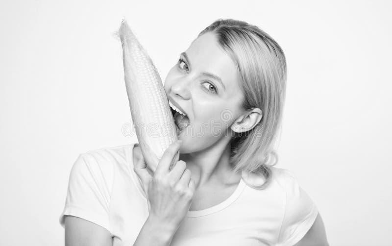 Gezonde tanden honger Het ploegen van het gebied De gelukkige vrouw eet graan plantaardige oogst die, landbouwersmeisje met ma?s  royalty-vrije stock fotografie