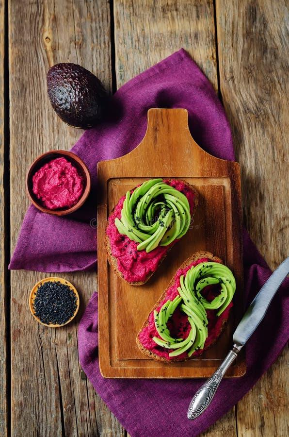 Gezonde van de de avocadorogge van bietenhummus het ontbijtsandwiches stock afbeeldingen