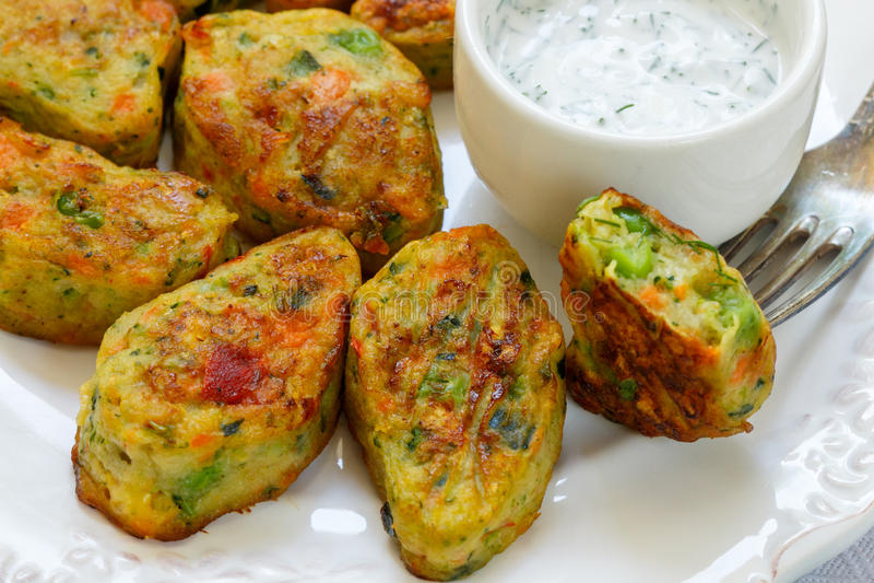 Gezonde vegetarische aardappelpasteitjes met wortelen, broccoli, groene paprika, groene erwten en uien met zure roomsaus met dill stock afbeelding