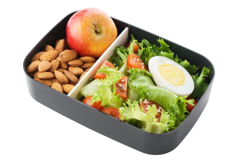Gezonde vegetarische lunchdoos met salade, noten en appel isoleer stock afbeelding