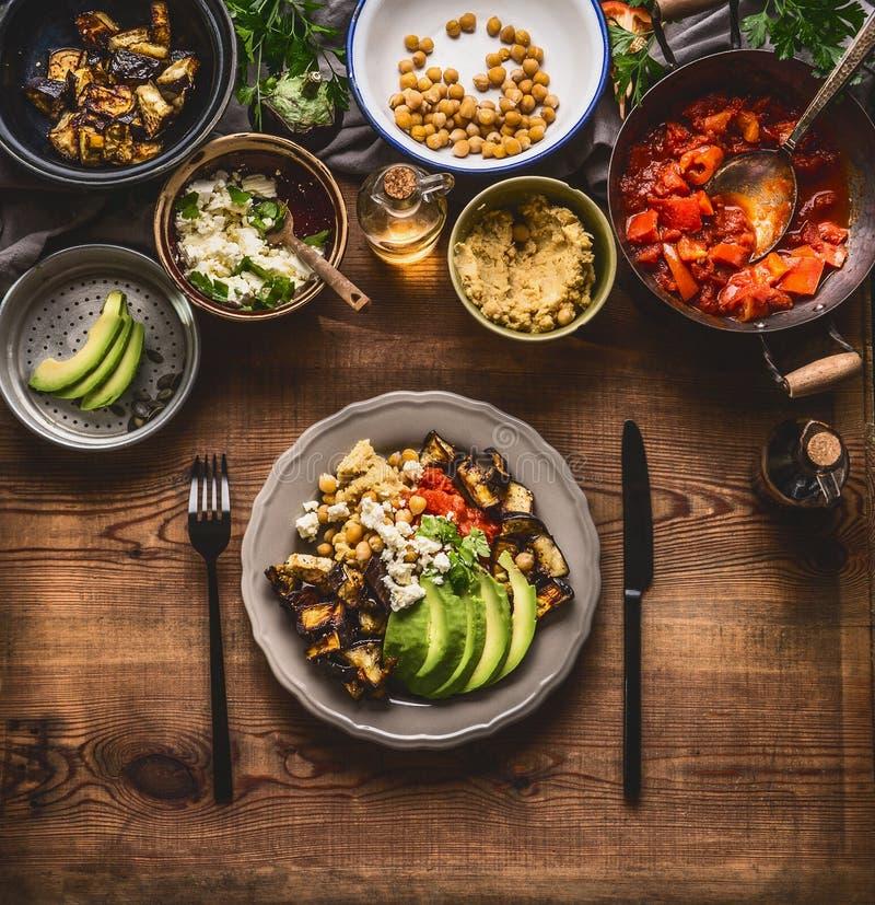 Gezonde vegetarische maaltijd De kom met kekerspuree, geroosterde groenten, rode paprikatomaten stooft, avocado en zaden Schoon e stock foto's