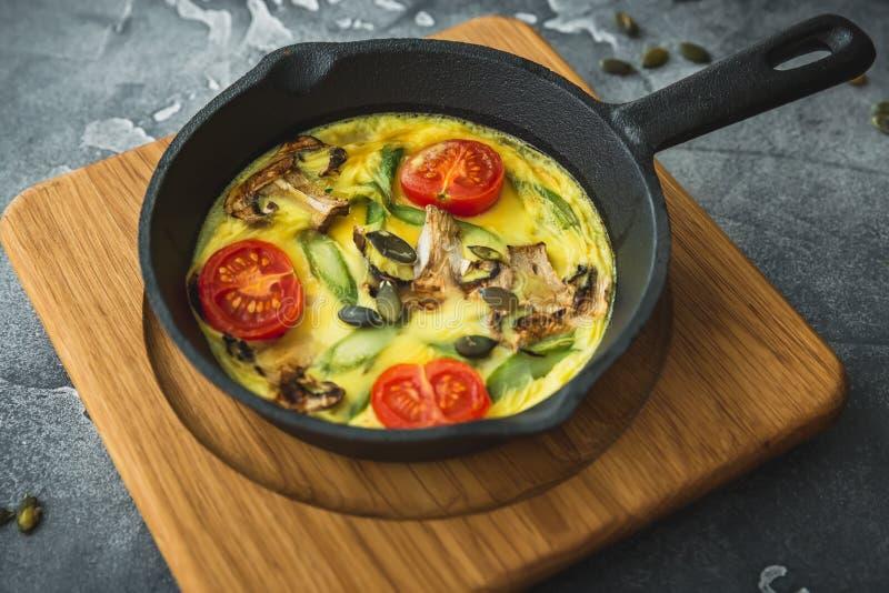 Gezonde vegetarische omelet in pan en pompoenzaden op houten raad royalty-vrije stock foto