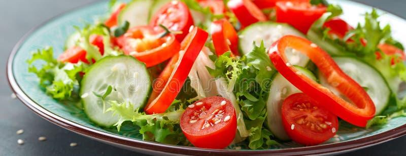Gezonde vegetarische plantaardige salade van verse sla, komkommer, paprika en tomaten Veganist op installatie-gebaseerd voedsel stock foto