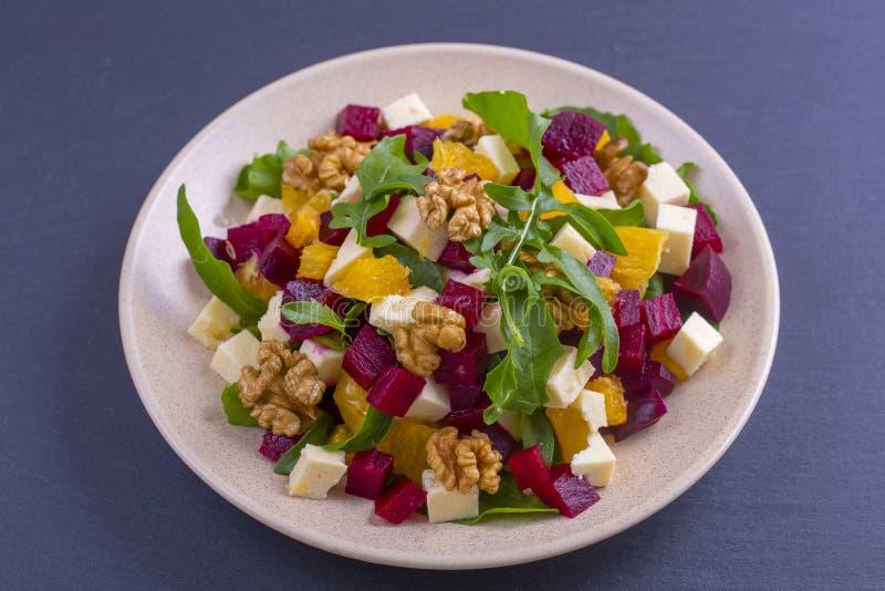 Gezonde vegetarische salade met bieten, groene arugula, sinaasappel, feta-kaas en okkernoten op plaat stock afbeelding