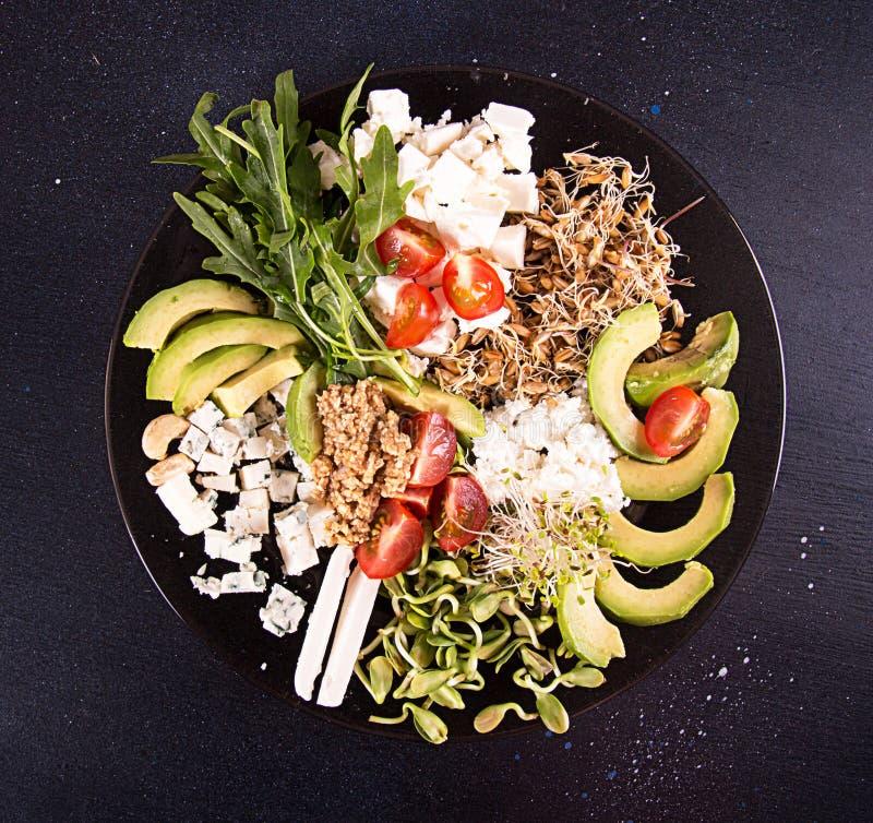 Gezonde vegetarische salade van avocado, kersentomaat, spruiten, arugula, feta; schimmelkaas, graangewassen Gezond het eten voeds stock foto
