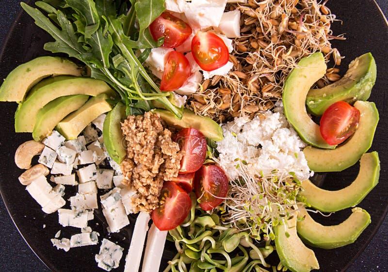 Gezonde vegetarische salade van avocado, kersentomaat, spruiten, arugula, feta; schimmelkaas, graangewassen Gezond het eten voeds stock foto's