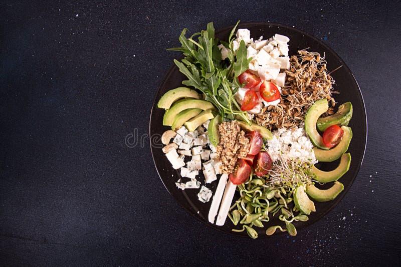 Gezonde vegetarische salade van avocado, kersentomaat, spruiten, arugula, feta; schimmelkaas, graangewassen Gezond het eten voeds stock fotografie