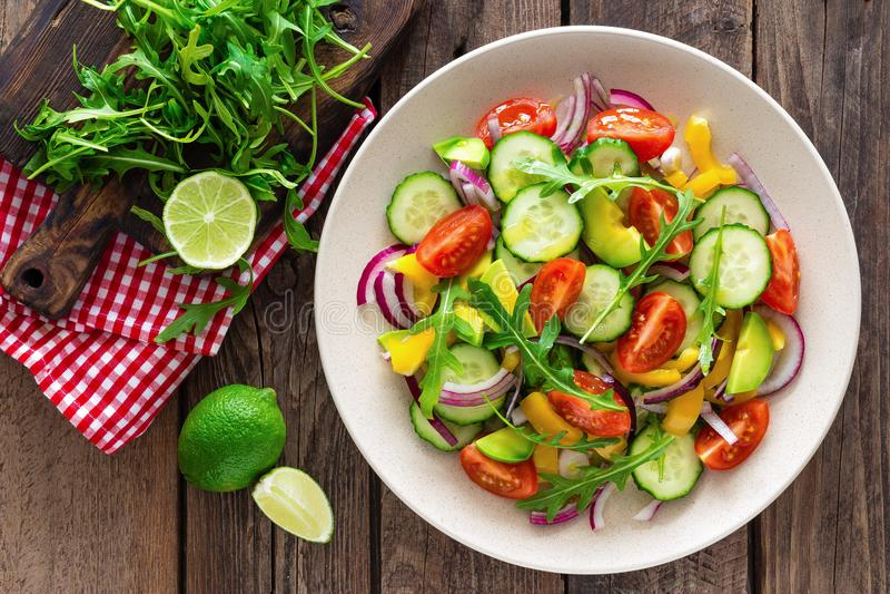 Gezonde vegetarische schotel, plantaardige salade met verse tomaat, komkommer, groene paprika, rode ui, avocado en arugula stock foto's