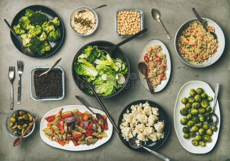 Gezonde vegetarische schotels in platenans kommen op concrete lijst royalty-vrije stock foto
