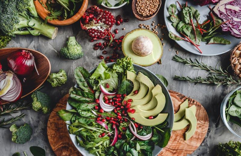 Gezonde verse salade met avocado, greens, arugula, spinazie, granaatappel in plaat over grijze achtergrond Gezond veganistvoedsel