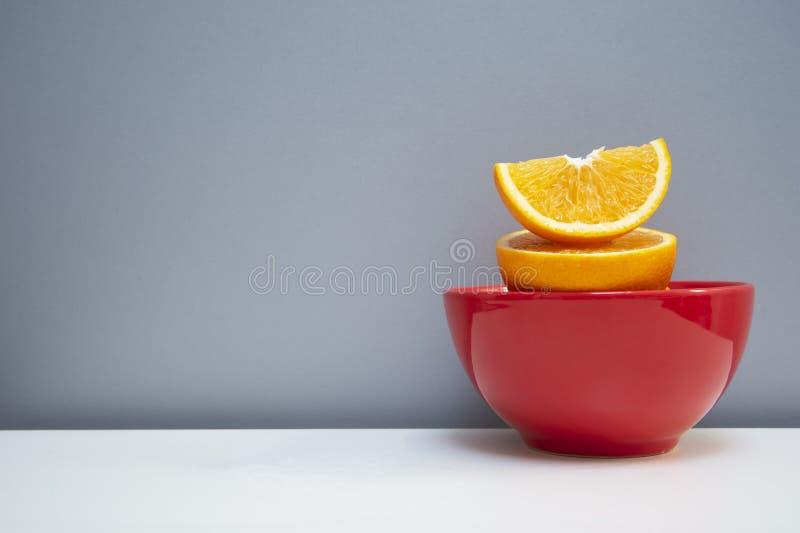Gezonde versheids sappige plak en halve besnoeiing van oranje fruit voor voedsel in rode ceramische kom op witte lijst met grijze stock fotografie