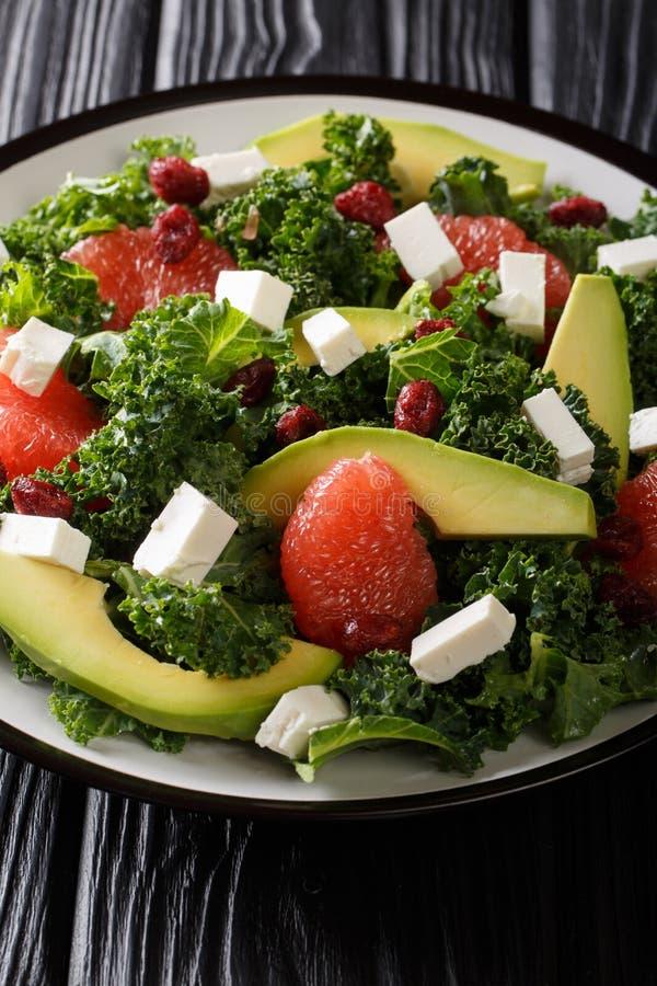 Gezonde vitaminesalade van boerenkool, avocado, grapefruit, kaas en droog Amerikaanse veenbessenclose-up op een plaat verticaal stock afbeeldingen