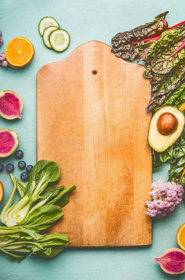 Gezonde voedselachtergrond met diverse verse vruchten en groenten rond scherpe raad op lichte muntachtergrond, hoogste mening royalty-vrije stock fotografie