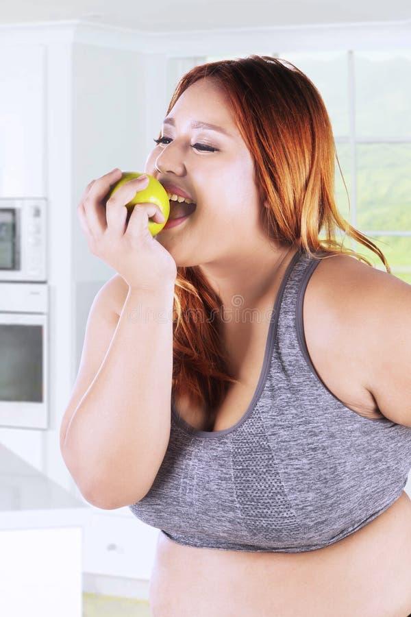 Gezonde vrouw die appel in keuken eten stock fotografie