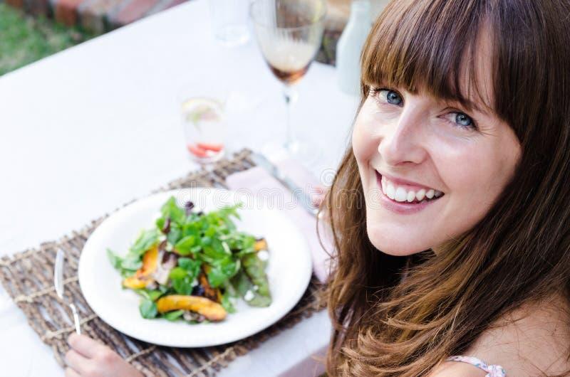 Gezonde vrouw die salade in openlucht eten stock fotografie