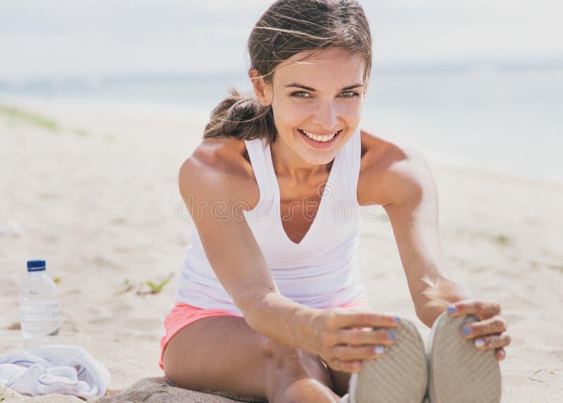 Gezonde vrouw die terwijl het doen van been het uitrekken glimlachen stock afbeelding