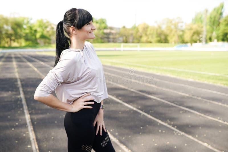 Gezonde vrouw met het exemplaar ruimte lichte achtergrond van de sportslijtage Het meisje van de geschiktheid gelukkig ontspan he stock afbeeldingen