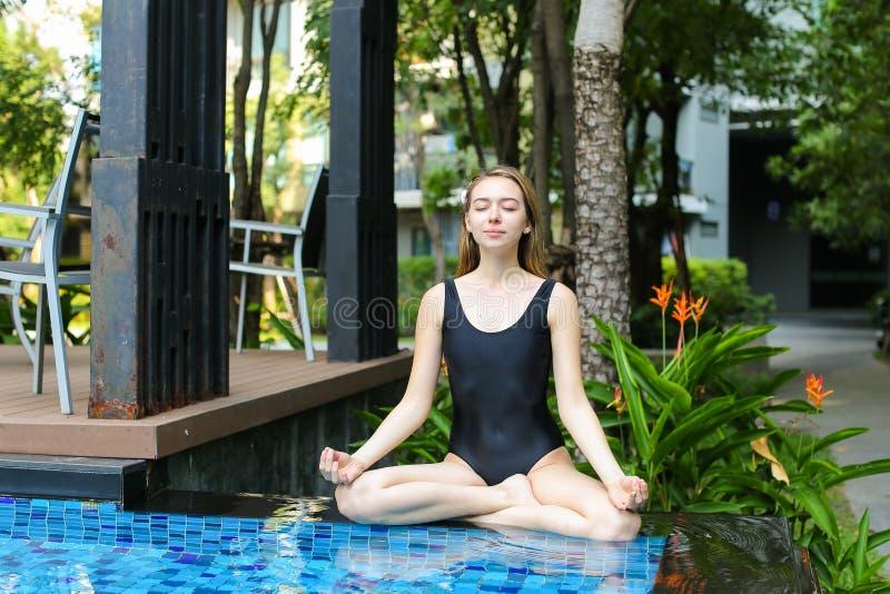 Gezonde vrouwenzitting in lotusbloempositie, die yoga doen door de pool royalty-vrije stock foto