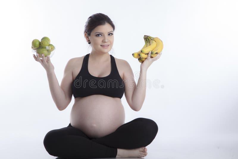 Gezonde zwangere vrouw die fruit eten royalty-vrije stock afbeeldingen
