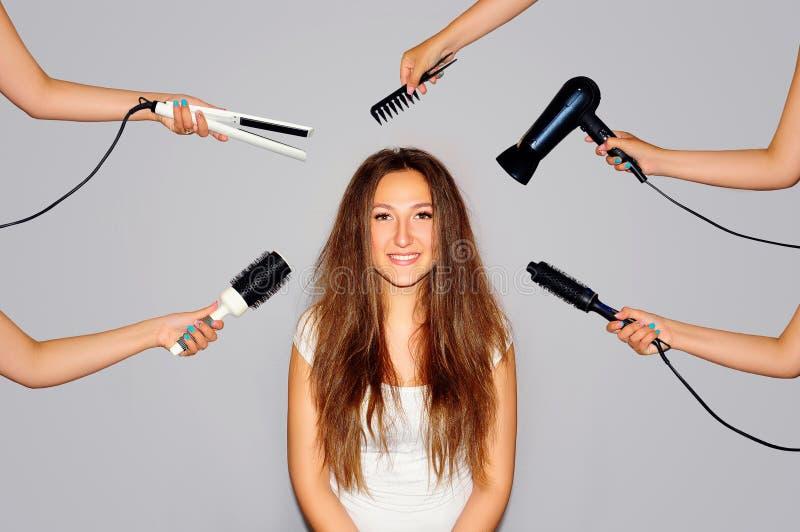 Gezondheid en schoonheid Jonge vrouw die een schoonheid en een haarstijl in dezelfde tijd die met handen krijgen de verschillende stock foto