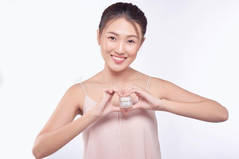 Gezondheid en schoonheidsconcept - Aantrekkelijke Aziatische vrouw die room op haar huid toepassen royalty-vrije stock afbeeldingen