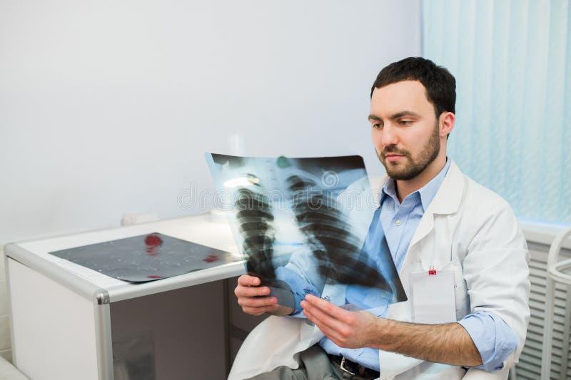 Gezondheid en stemming Het ernstige Arts spreken aan patiënt houdt borströntgenstraal in handen terwijl het zitten van bij een li stock foto's