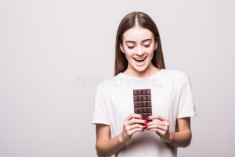 Gezondheid, mensen, voedsel en schoonheidsconcept - Mooie glimlachende vrouw die die chocolade eten op grijze achtergrond wordt g stock afbeelding