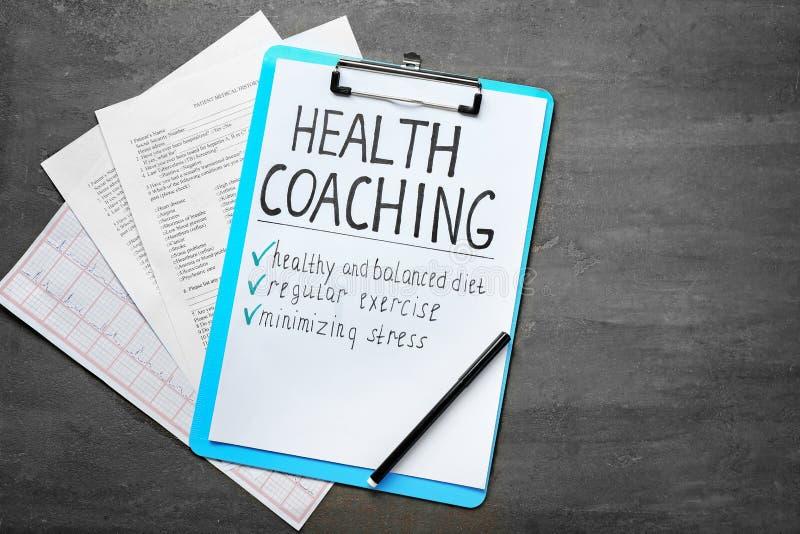 Gezondheid trainen geschreven op blad van document met medische documenten op grijze achtergrond stock afbeelding