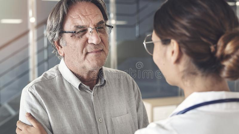 Gezondheidsarbeider die aan de patiënt spreken stock foto