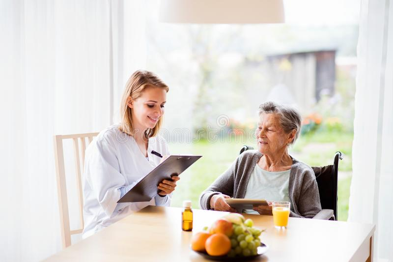 Gezondheidsbezoeker en een hogere vrouw met tablet stock foto