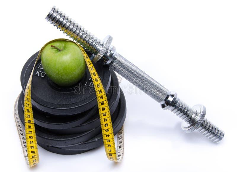 Gezondheidsconcept, een appel met een meetlint en gewichten stock afbeelding