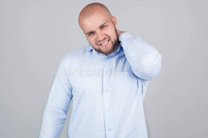Gezondheidsprobleemconcept De gefrustreerde jonge Kaukasische mens heeft halspijn, kijkt met droevige uitdrukking, draagt wit ove stock fotografie