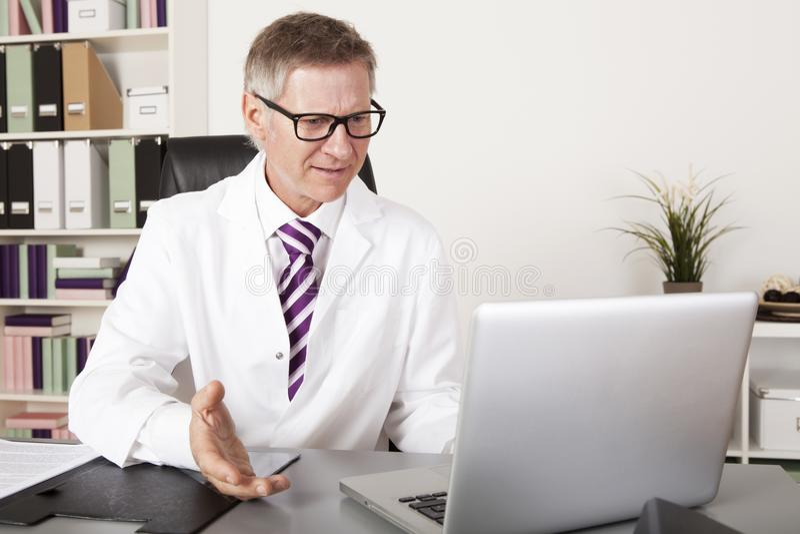 Gezondheidswerker Sprekende Cliënt die Laptop met behulp van stock afbeelding