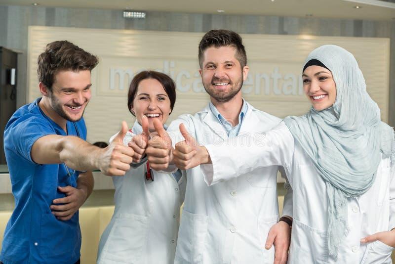 Gezondheidszorg en geneeskundeconcept - de aantrekkelijke mannelijke arts voor medische groep in het ziekenhuis het tonen beduime stock fotografie