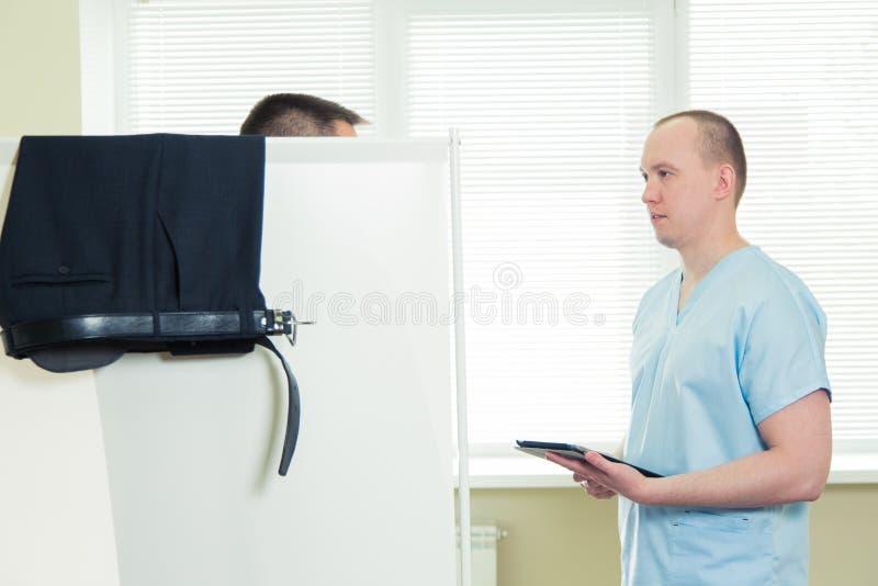 Gezondheidszorg, het concept van de technologiegeneeskunde - ernstige arts met en patiënt in het ziekenhuis achter het Gordijn stock afbeelding