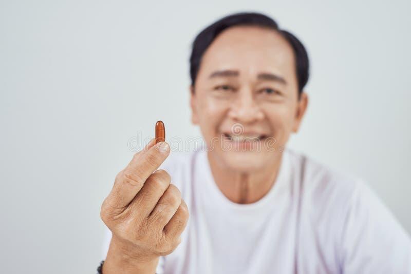 Gezondheidszorg, madicine, apotheek en bejaard concept - oude mens met pillen stock fotografie