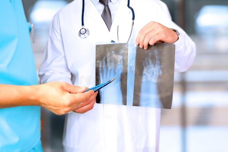 Gezondheidszorg, medische en radiologieconcept - Mannelijke artsen die röntgenstraal van voet bekijken stock afbeelding