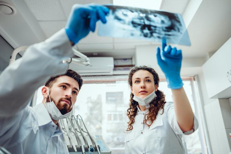 Gezondheidszorg, medische en radiologieconcept - twee tandarts artsen die röntgenstraal bekijken Selectieve nadruk royalty-vrije stock foto