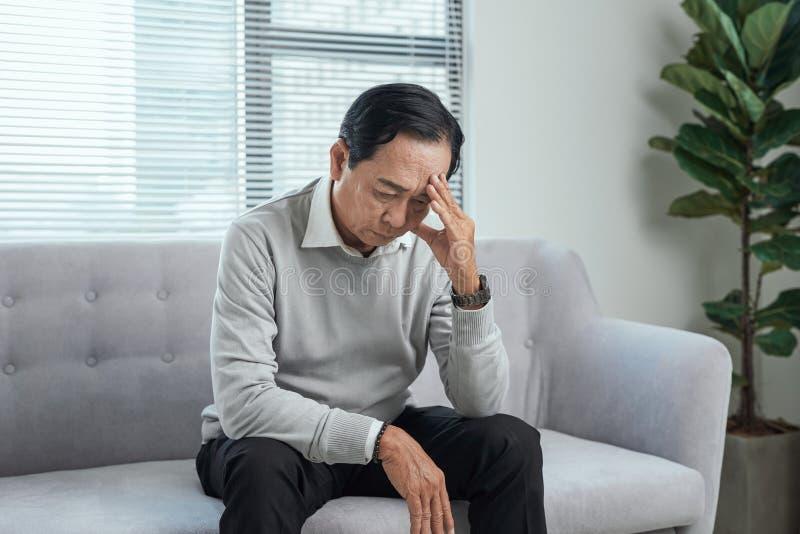 Gezondheidszorg, spanning, oude dag en mensenconcept - hogere mens die aan hoofdpijn thuis lijden stock afbeelding