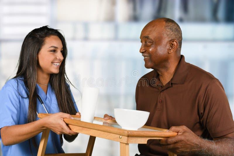Gezondheidszorgarbeider en het Bejaarde Geduldige Eten stock afbeelding