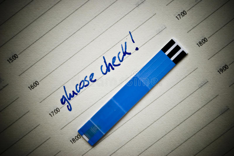 Gezondheidszorgconcept. Strepen voor glucose test en het eraan herinneren van nota in persoonlijke organisator. Concept betreffend stock fotografie