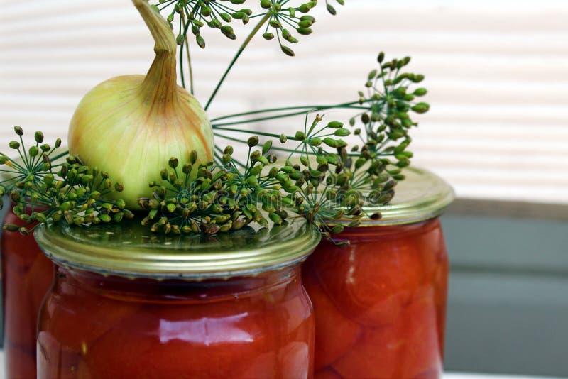 Gezouten die tomaten in een kruik met marinade worden gerold stock afbeeldingen