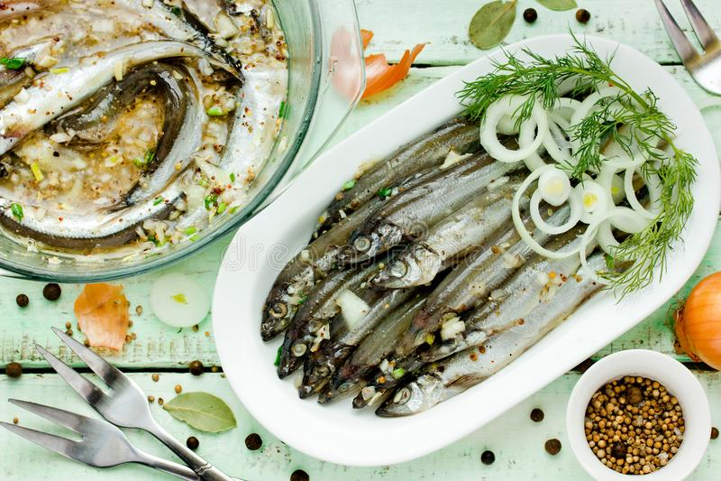 Gezouten die vissen met kruiden worden gemarineerd royalty-vrije stock afbeeldingen