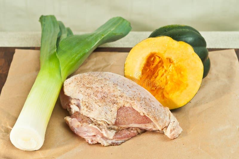 Gezouten en peppered ruw, organisch, kippenborst, gewassen prei, op een bamboe houten scherpe raad, stock afbeelding