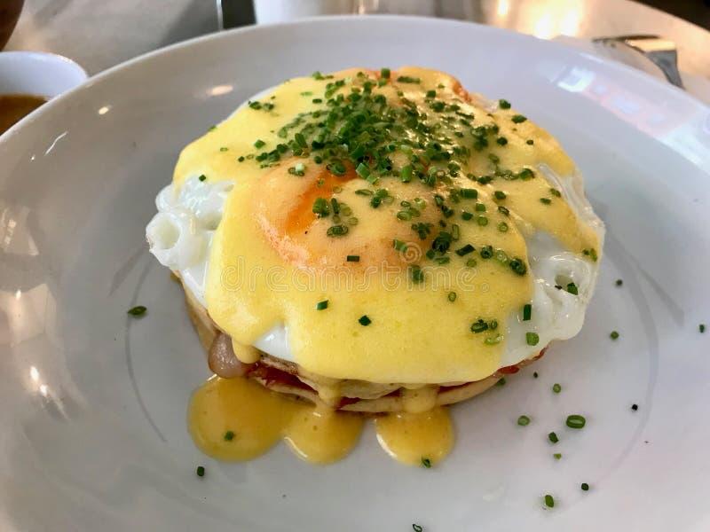 Gezouten Pannekoeksandwich met Fried Eggs, Hollandaise-Saus Knapperig Bacon en Bladeren van de Sjalot de Groene Ui stock foto's