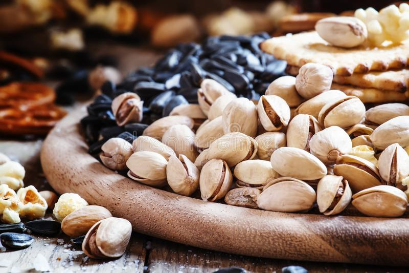 Gezouten pistaches, popcorn en andere zoute snacks op houten pl royalty-vrije stock afbeeldingen