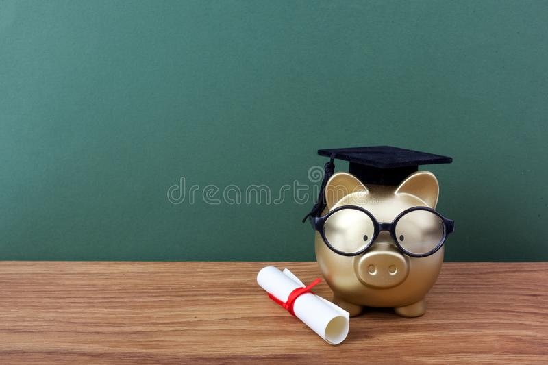 Gold piggy bank with a grad cap and diploma in front of green chalkboard. Education scholarship. Gold piggy bank with a grad cap and diploma in front of green royalty free stock photography