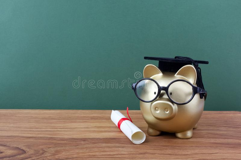 Gold piggy bank with a grad cap and diploma in front of green chalkboard. Education scholarship. Gold piggy bank with a grad cap and diploma in front of green royalty free stock photo