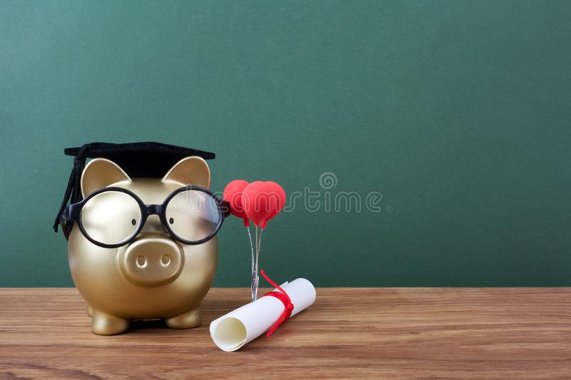 Gold piggy bank with a grad cap and diploma in front of green chalkboard. Education scholarship. Gold piggy bank with a grad cap and diploma in front of green royalty free stock photos