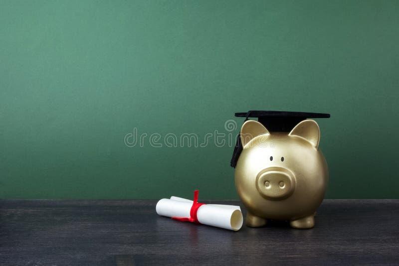 Gfold spargris med ett akademikert lock och diplom framme av den gröna svart tavlan Utbildningsstipendium royaltyfria foton